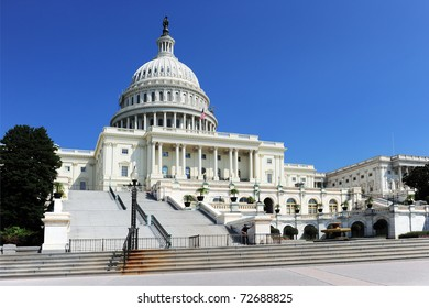 A view of the United States Congress Building against a clear, deep blue sky.