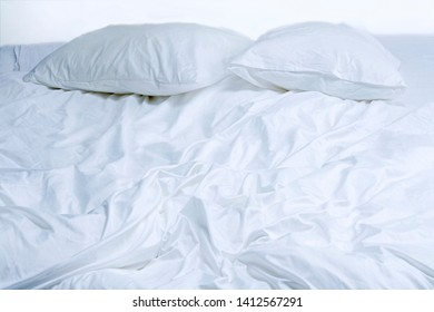 View of unmade bed with cushions and blankets.