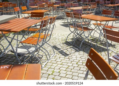 A view of unoccupied wooden tables and chairs outside on a sunny day