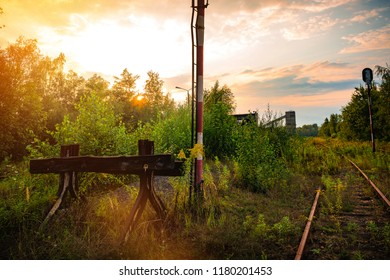 View of unused railway tracks and end of tracks with a blockade on the background of the setting sun. Industrialism in Silesia. A view on the restructuring of mining and mine removal.