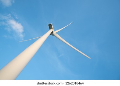 View up, bottom view of wind turbine, windmill isolated on blue sky background. Royalty high-quality free stock photo image looking up wind turbine, windmill energy converter in a blue sky background