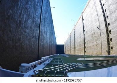 The view from the upper deck of a boat as it passes through a lock. The boat is almost touching both sides of the lock, which rise above it to a blue sky. Lights overhand the concrete walls.