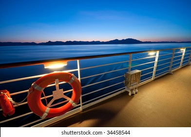 View from the upper deck of a cruise ship sailing in Alaska at dusk.
