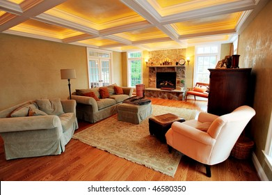 View of an upscale living room interior with a box beam ceiling. Horizontal format.