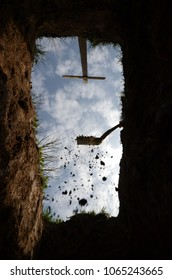View upwards from the bottom of a grave, a last glimpse of the sky. The gravedigger has started to cover the grave.