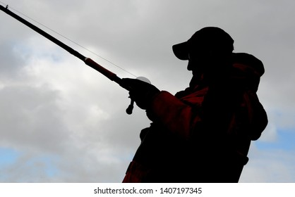 View upwards at a muskie angler in a baseball cap silhouetted against a bright partly cloudy sky with a musky fishing rod and reel combo fishing