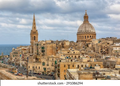 View to Valetta city buildings including Our Lady of Mount Carmel and St Pauls Pro-Cathedral under clouds, Malta