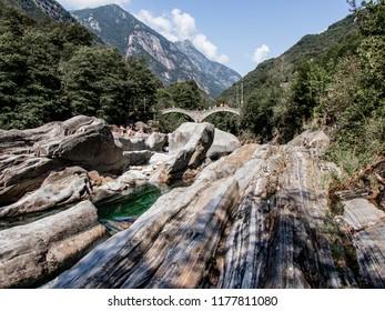View in Valle Verzasca, famous Swiss Location with double arch stone bridge at Ponte dei Salti with waterfall, Lavertezzo, Verzascatal, Canton Tessin – Tecino