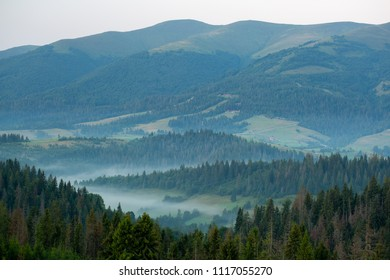 view of a valley in a beautiful early morning with fog between mountains
