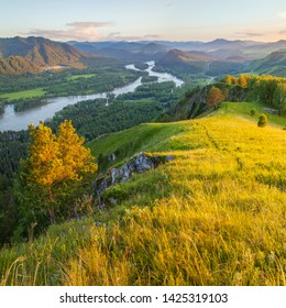 View of the valley and the Katun River from the mountain. Spring panoramic view. Evening light.