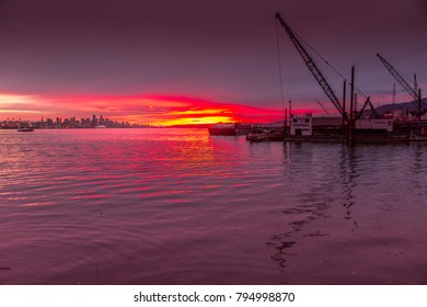 View of Vancouver Skyline and cranes of the dockyards of North Vancouver at sunset, British Columbia, Canada, North America 16 September 2017