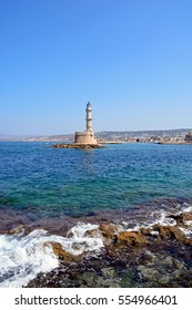 View of the Venetian lighthouse at the harbour entrance with rocks in the foreground, Chania, Crete, Greece, Europe.