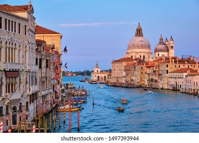 View of Venice Grand Canal with boats and Santa Maria della Salute church on sunset from Ponte dell'Accademia bridge. Venice, Italy