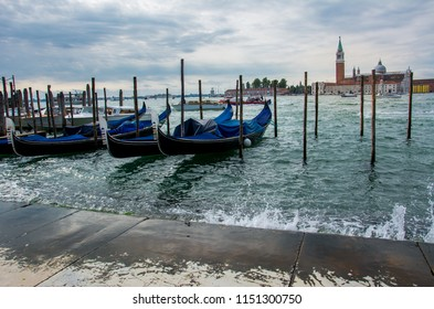 View of Venice Lagoon with gondolas waiting for tourists and San Giorgio Maggiore island in the background. Venice, located in Italy, is one of the most popular tourist destinations in the world