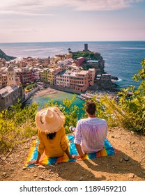 View of Vernazza one of Cinque Terre in the province of La Spezia, Italy, happy young couple picnic in the mountain with a look over the ocean
