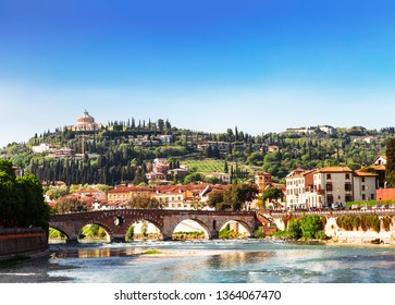 View of Verona with Ponte Pietra bridge over the Adige river and the Sanctuary of our lady of Lourdes on a hill, Italy