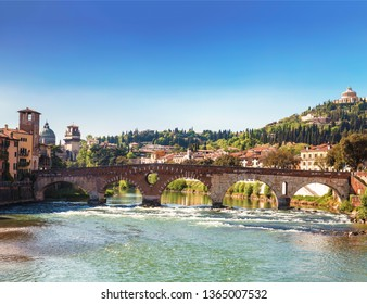 View of Verona with Ponte Pietra bridge with watchtower over the Adige river and the Sanctuary of our lady of Lourdes on a hill, Italy