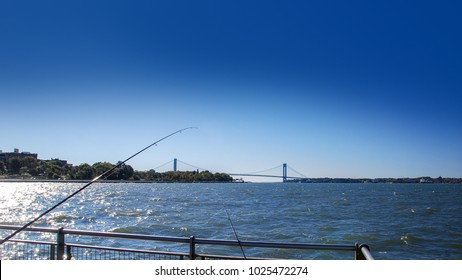 view to the Verrazano Narrows Bridge from the Brooklyn with fishing rods on foreground