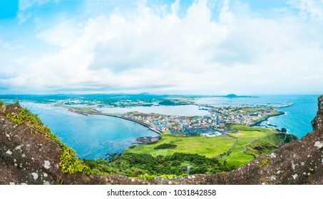 View from the very top of famous Seongsan mountain on a windy day at the shore of volcanic origin Jeju Island - South Korea