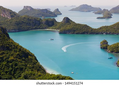 View from the viewpoint deck in Koh Wua Ta Lap, boat floating and running on blue turquoise ocean and group of islands in Ang Thong National Marine Park in the Gulf of Thailand. Surat Thani, Thailand