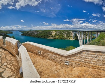 View from the viewpoint on the Sibenik Bridge a long concrete arch bridge passing through the canyon of the Krka River. Location Skradin town, Croatia, Europe. Scenic image of travel destination.