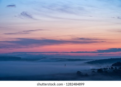 View of village covered in fog during morning sunrise. South moravian landscape with low clouds during a sunrise. Hazy summer scene of small village.