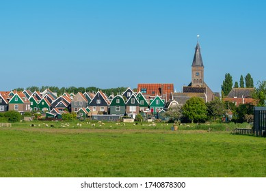 View of the village of Marken in the Netherlands with sheep grazing in the forefront.