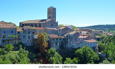 A view of the village of Montolieu Aude  Languedoc - Roussillon  France. Trees valley ancient houses and church bell tower.