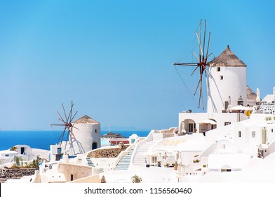 View of the village of Oia, Santorini, Greece, Europe. Beautiful classical white Greek architecture with windmills on the volcano of Santorini. Cycladic island of Caldera, the Aegean Sea in Greece.