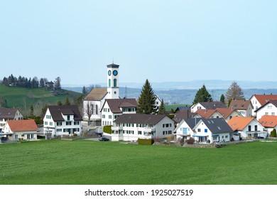 View of the village Schönenberg, Switzerland, with surrounding fields and hills