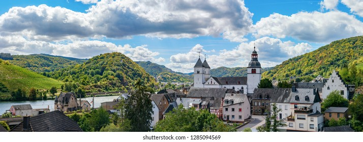 View of the village Treis-Karden with the Saint Castor abbey church, the Moselle and the surrounding hills on the background on a summer day. Cochem-Zell; Rhineland-Palatinate, Germany.