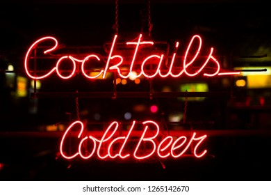 View at vintage coktails and cold beer neon sign hanging in a bar window