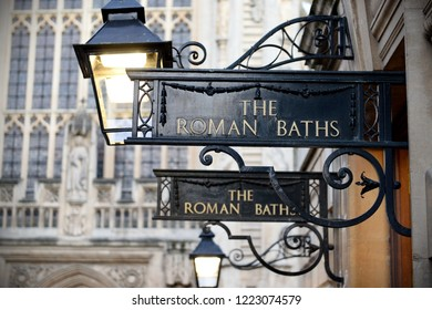 View of Vintage Signs and Street Lamps at the Entrance of the Historic Roman Baths in the City of Bath in Somerset England