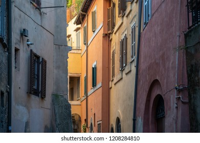 View of vintage windows with antique louvered shutters on the side wall of a very old building in Italy showing rich tones and textures.