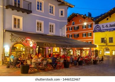 View of visitors enjoying drinks outside cafe on Vorderstadt at dusk, Kitzbuhel, Austrian Tyrol Region, Austria, Europe 1-5-2019