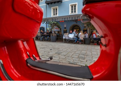 View of visitors enjoying drinks outside cafe framed by red scooter on Vorderstadt, Kitzbuhel, Austrian Tyrol Region, Austria, Europe 1-5-2019