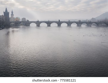 View of the Vltava River and the Charles Bridge from Manes Bridge in foggy morning.