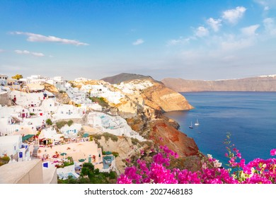 view of volcano caldera with colorful houses of Oia, Santorini island with fllowers, Greece