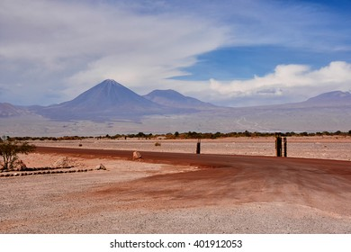 The view of the volcano Licancabur. Chilie in the clouds. In the foreground the deserted dirt road
