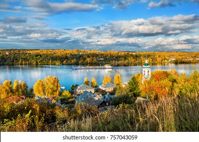 A view of the Volga River from the Levitan Mountain in the autumn Plyos and the Varvara Church, and the barge sails along the river