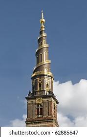 View of the Vor Frelsers Kirke Tower in Copenhagen, Denmark against deep blue sky