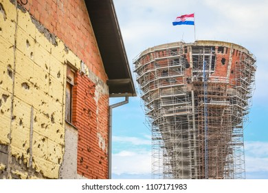 A view of the Vukovar water tower under reconstruction with a house damaged in war in Vukovar, Croatia. The water tower is a symbol of the city suffering in the Croatian War of Independence.