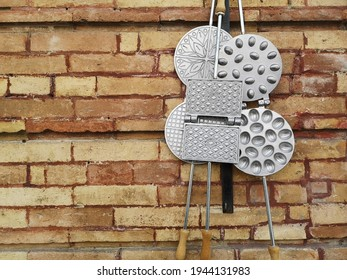 A view of waffle molders hanging against a brick wall in Abruzzo, Italy