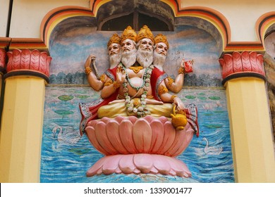 View of wall art of Hindu god Brahma. Brahma, the four-headed lord, sits on a lotus flower. Religious image on the temple in India.