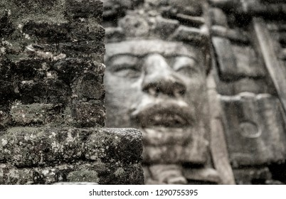 View of the wall of the Mayan temple of Lamanai, with out of focus stone face in background.
