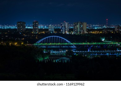 A view of the Walterdale Bridge, crossing over the North Saskatchewan River in Edmonton, Alberta, Canada at night. Condos along North Saskatchewan Drive are visible behind. Taken on August 30, 2018.