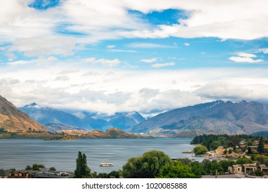 View of Wanaka lake and alpine resort town with the mountain range in the background on a cloudy summer day. Wanaka is a popular ski resort town in New Zealand, South Island.