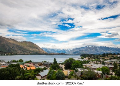 View of Wanaka lake and alpine resort town in New Zealand with the mountain range in the background on a fair summer day.