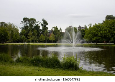 View of water fountain, pond, trees, people walking and riding bicycles at Vondelpark in Amsterdam. It is a public urban park of 47 hectares. It is a summer day.