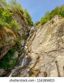 view of waterfall on steep rock ravine , shot on a bright summer day at Gressoney Saint Jean,  Lys valley, Aosta, Italy